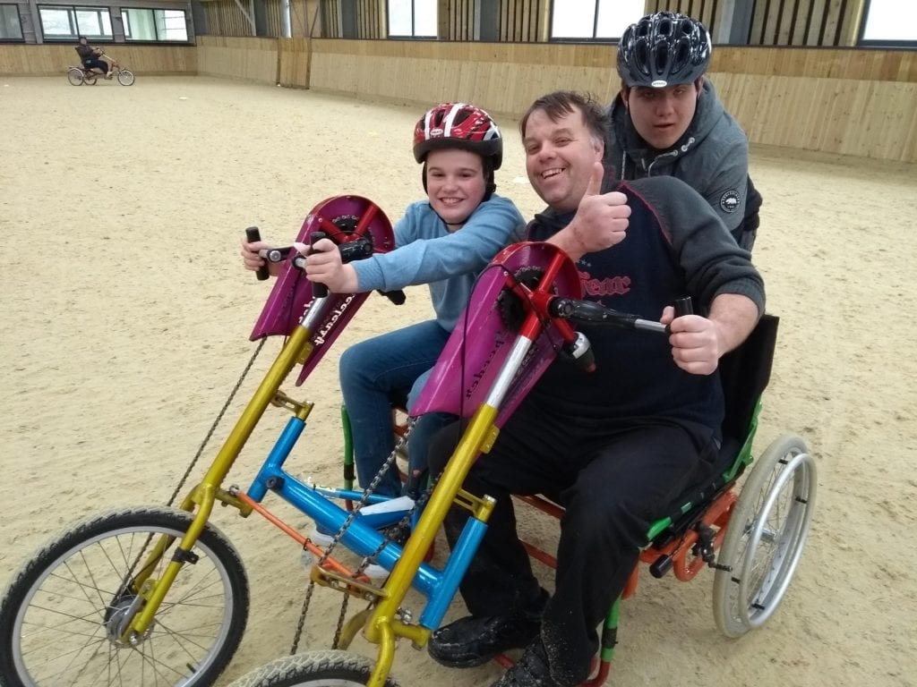 Group of people smiling inside an accessible bike