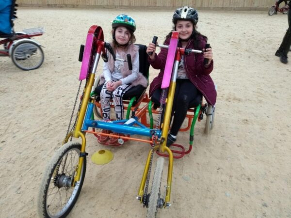 People smiling inside an accessible bike