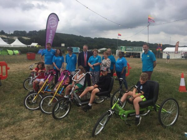 Picture of isle access trustees next to a group of people on accessible bikes