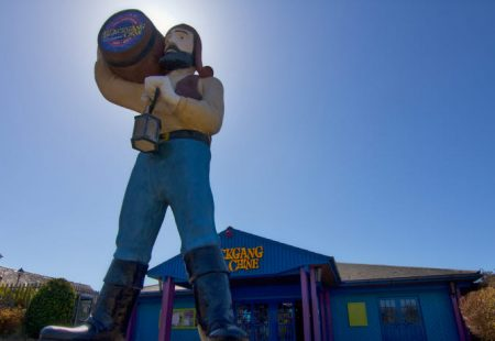Blackgang Chine - Picture of a statue holding a barrell with blue sky in the background.