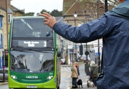 Isle of wight bus with a man holding his hand out to make it stop