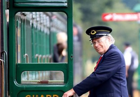 Picture of a conductor next to a train at the Isle of Wight Railway.